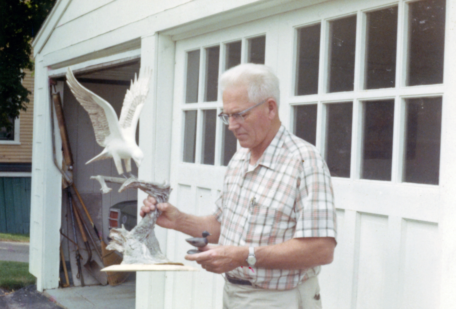 Wendell H. Gilley Holding Eagle Carving and Miniature Mallard, Summer 1971